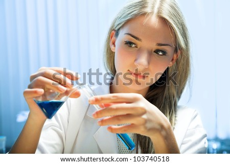 female researcher look at retort with blue liquid