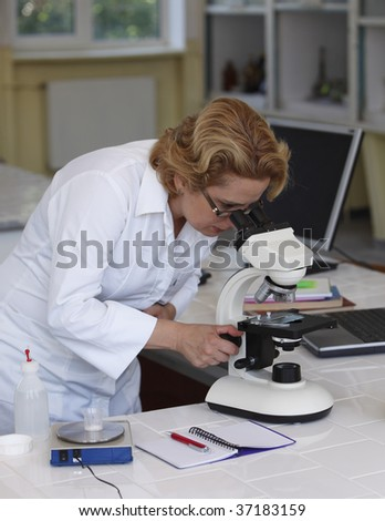 Female researcher looking in a hurry through a microscope in a laboratory. - stock photo