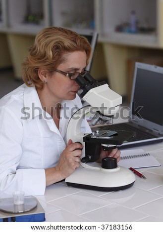 Female researcher looking through microscope in a laboratory.