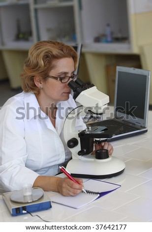 Female researcher taking notices while she is using a microscope.
