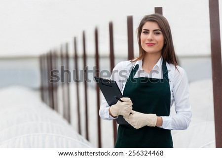 Female researcher technician studying with a clipboard, pen and gloves, dressed in office clothes,office shirt and apron, in all withe greenhouse. - stock photo