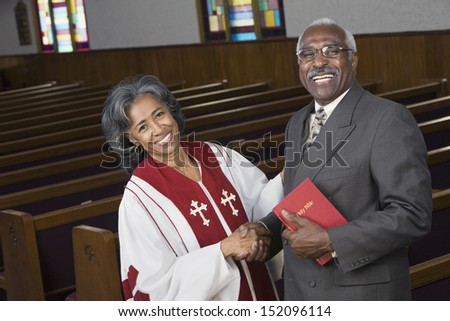 Female Reverend shaking hands with parishioner - stock photo