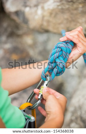 Female rock climber adjusting her harness by the rock face - stock photo