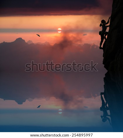 Female rock climber and mountain sunset. Silhouette of elegant female extreme climber surrounded by alpine landscape with lake and bright red sunset