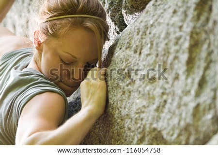 Female rock climber climbing a stone structure - stock photo