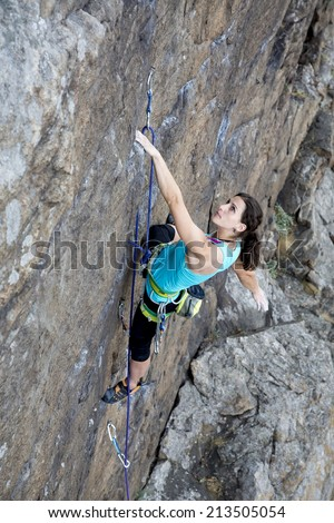 Female rock climber hanging over the abyss. Brave and confident female rock climber enjoys hanging on her hand over the deep abyss.
