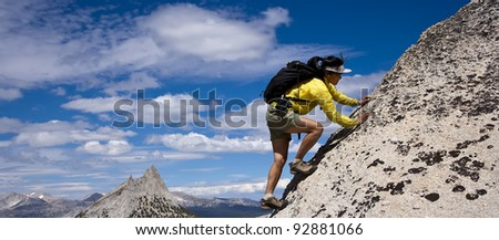 Female rock climber struggles to grip the edge on a challenging cliff. - stock photo