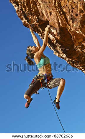 Female rock climber struggles up a cliff for her next grip on a challenging ascent. - stock photo