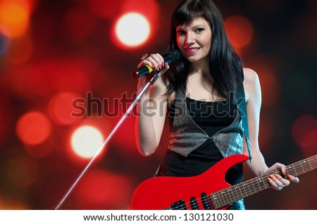 Female rock star with electric guitar over bright background - stock photo