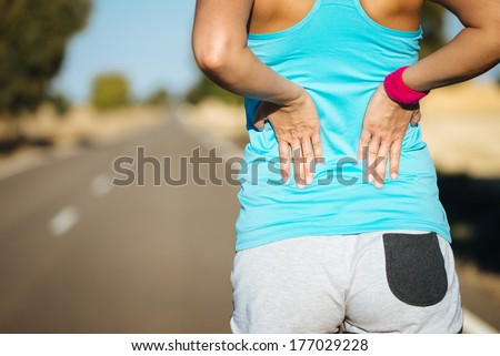 Female runner athlete back injury and pain. Woman suffering from painful lumbago or kidney illness while running in rural road. - stock photo