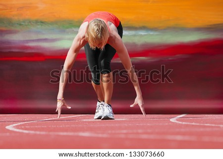 Female runner in start position with canvas in the background