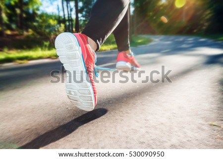Female runner jogging down an outdoor trail at sunset