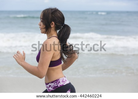 Female runner jogging during outdoor workout on the beach - stock photo