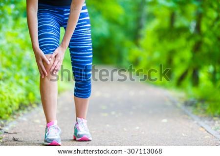 Female runner knee injury and pain. - stock photo