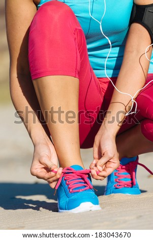 Female runner lacing sport footwear before running and fitness exercising on beach. - stock photo