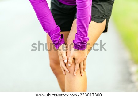 Female runner leg and muscle pain during running outdoors in summer nature, sport jogging physical injury working out outside holding sore knee joint. Health and fitness concept accident when training - stock photo