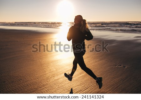 Female Runner on the Beach at Sunset silhouette in air - stock photo