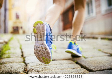 Female runner running on tiled pavement in city center, closeup on shoes - stock photo