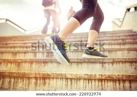 Female runner running up the stairs in city center, closeup on shoes - stock photo