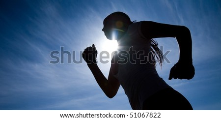 Female runner silhouette against the blue sky and sun - stock photo