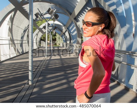 Female Runner smiling and running on a modern bridge. Wellness and healthy lifestyle concept.