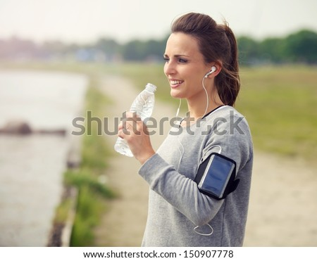 Female runner smiling while drinking bottled water - stock photo