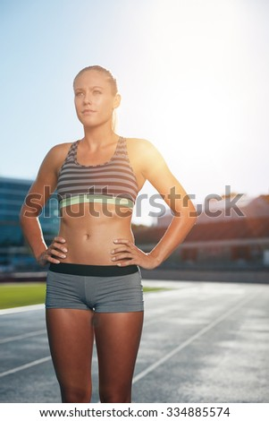 Female runner standing with her hands on hips looking away. Determined woman athlete on race track in athletics stadium with sun flare. - stock photo