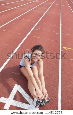 Female runner stretching her legs on a track