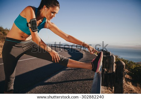 Female runner stretching her legs outdoor before running. Woman doing leg stretch exercises on road guardrail. - stock photo