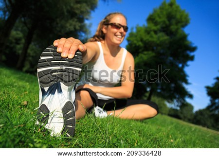 Female runner stretching her muscles in the park before a training. - stock photo