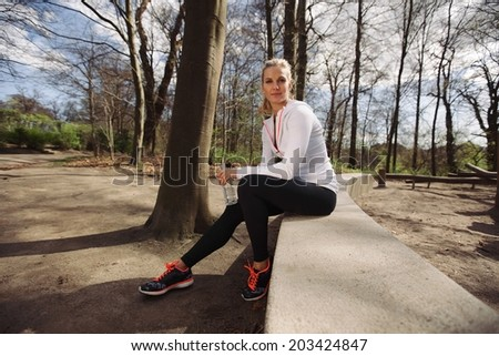 Female runner taking a rest from training in nature. Attractive young woman sitting relaxed with a water bottle.