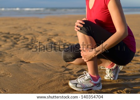Female runner tibia muscle cramp. Woman clutching her shin because of a running injury and inflammation. Tibial periostitis hurt while jogging on beach. - stock photo
