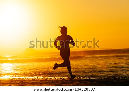 Female runner training hard on beautiful summer sunset or morning. Woman running fast at the beach.