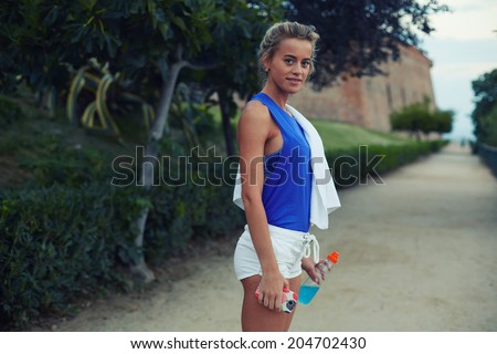 Female runner with beautiful figure standing in big green park at evening jog, sporty girl with bottle of water in the hands, fitness and healthy lifestyle concept