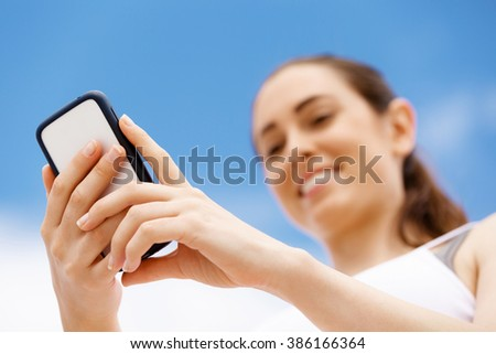 Female runner with her mobile smart phone standing outdoors - stock photo