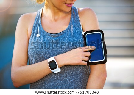 Female Runner With Mobile Phone And Smart Watch