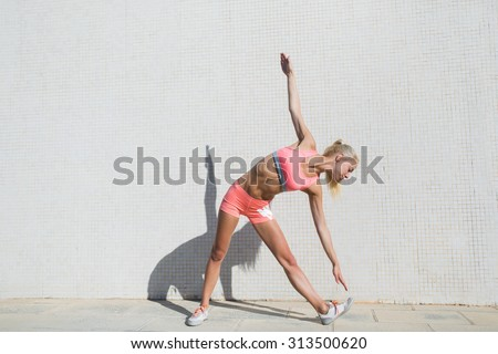 Female runner with perfect figure stretch body muscles while standing against street wall background with copy space area for your text message or content,fit woman doing warm up exercises before run - stock photo