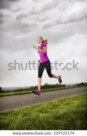 Female Runner working out dramatic clouds - stock photo