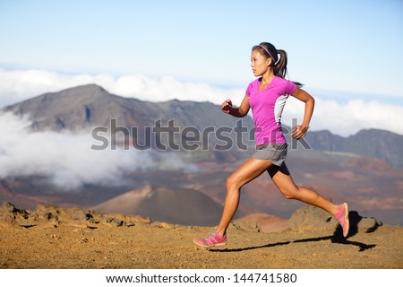 Female running athlete. Woman trail runner sprinting for success goals and healthy lifestyle in amazing nature landscape. Cross country run with fit female fitness model running at fast speed. - stock photo
