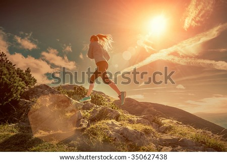 Female running in mountains under sunlight. - stock photo