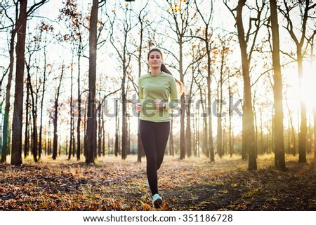 female running in park. Young woman jogging in autumn forest - stock photo