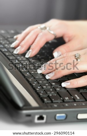 Female's hand with white nails touching a black metal keyboard. - stock photo