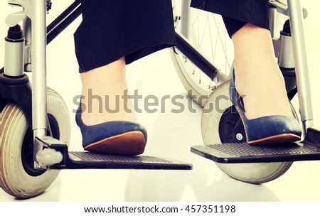 Female's legs and shoues on wheelchair. - stock photo