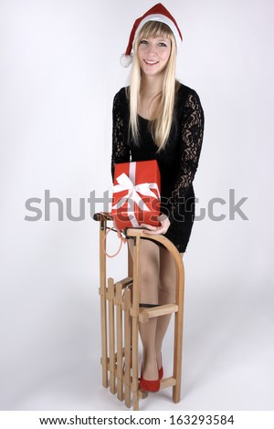 Female Santa Claus with a sleigh and a gift. - stock photo