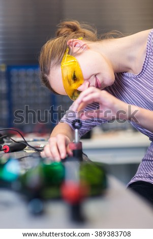 Female scientist carrying out research experiments in a quantum optics lab (color toned image) - stock photo