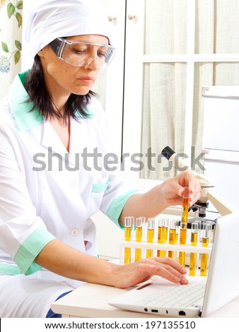 female scientist enters data into the computer in the life science research laboratory: biochemistry, genetics, forensics, microbiology - stock photo