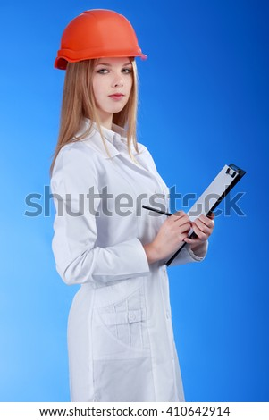 female scientist in helmet with pen and paper - stock photo