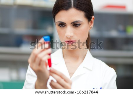 Female scientist looking at a test tube - stock photo