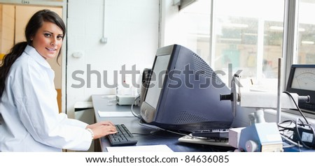 Female scientist with a monitor looking at the camera - stock photo