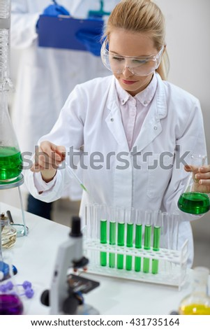 female scientist with pipette and flask making test or research in clinical laboratory